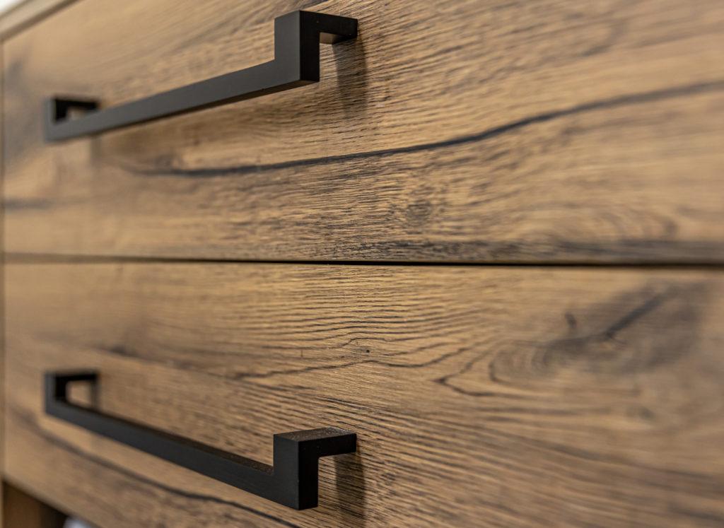 Close-up of modern dark wood furniture with black handles.